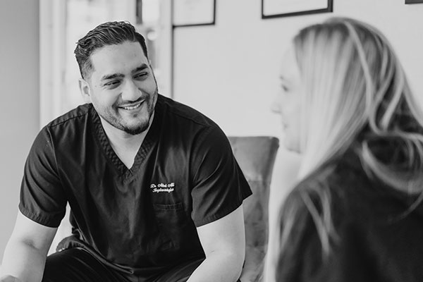 Dr Ali smiling whilst talking with patient